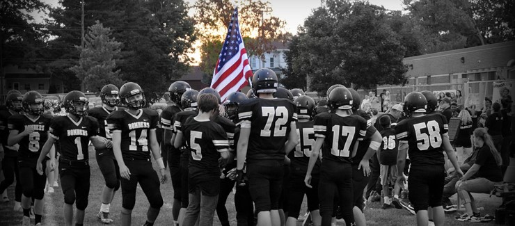 The football team carries out the flag prior to each home game.